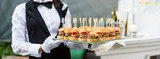 Fototapety Catering service. Waiter carrying a tray of appetizers. Outdoor party with finger food, mini burgers, sliders.