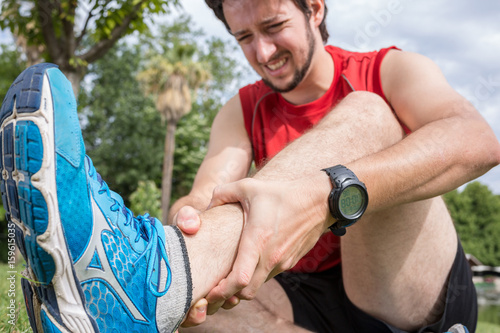 Staande foto Jogging Ankle injury while jogging, The man has wrong