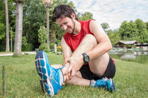 Fotobehang Hardlopen Ankle injury while jogging, The man has wrong