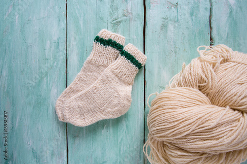 knitted socks and yarn on wooden surface