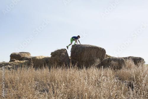 Plagát Boy (6-7) walking on bale of hay