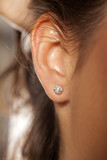 Closeup female ear with a small luxurious earring
