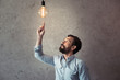 middle aged man pointing with finger at illuminated light bulb