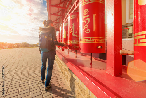Woman with backpack near red Buddhist drums in the sunlight