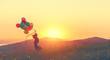 Leinwanddruck Bild - Happy cheerful girl with balloons running across meadow at sunset in summer