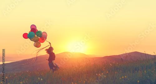 Leinwanddruck Bild Happy cheerful girl with balloons running across meadow at sunset in summer