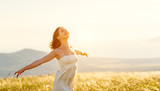 Happy woman standing with her back on sunset in nature iwith open hands