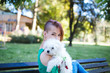 Portrait of beautiful smiling invalid young woman born without upper extremities holding her white little puppy and sitting on bench in park.