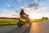 Motorbiker jazdy na pustej drodze z nieba słońca