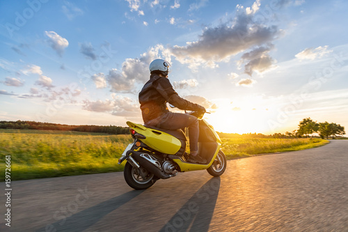 Motorbiker riding on empty road with sunset sky Poster