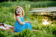 Cute blonde little baby girl sitting on the green grass in summer sunset.