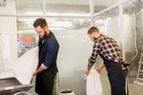 men with malt bags and mill at craft beer brewery - 159755294
