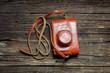 Постер, плакат: Старый фотоаппарат в чехле на деревянном столе