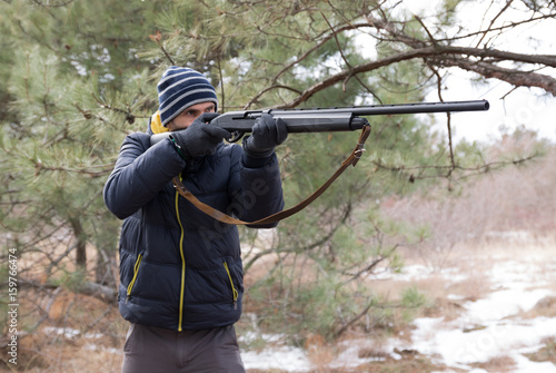 caucasian male in winter forest takes aim. Hunting with a shotgun