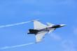 Modern jet fighter flying against a blue sky. White smoke trail.