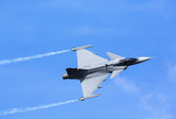 Modern jet fighter flying against a blue sky. White smoke trail. - 159804297