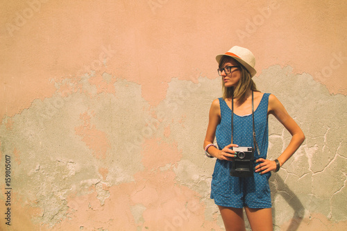 Attractive cute girl posing with retro film camera outdoors. Poster