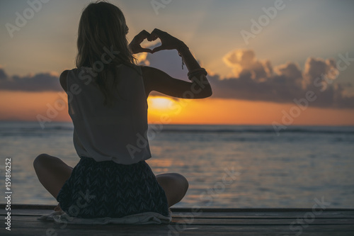 Girl holding a heart shape on the ocean / sea shore. Poster