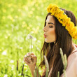 Beautiful Young Woman Blowing a Dandelion Outdoors