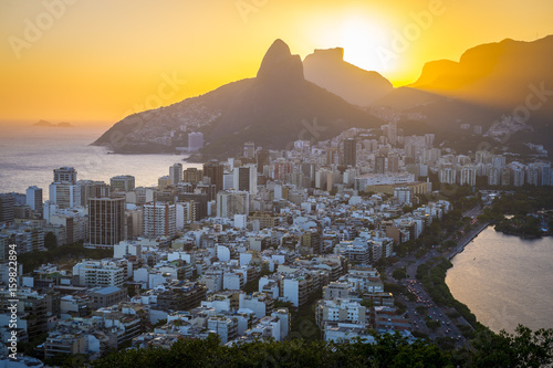 In de dag Rio de Janeiro A dramatic skyline view of sunset over Ipanema with Two Brothers Mountain looking over both the Atlantic Ocean and Rodrigo de Freitas lagoon with the skyscrapers of Ipanema and Leblon in between.