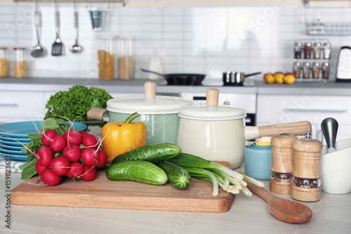 Fresh vegetables and utensils for cooking classes on wooden table