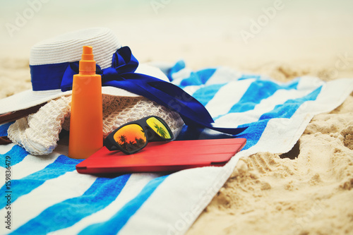 bag, suncream, glasses and touch pad on beach
