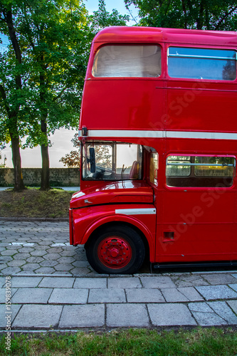Red two-story English bus standing in the park on the waterfront Poster