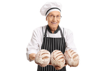 Cheerful baker with freshly baked loaves of bread