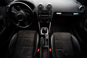 balck luxury car from inside. Close up of steering wheel, seat and circuit