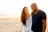Lovely black couple walking together on beach