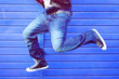 Man jumping wearing blue jeans on a dark blue background