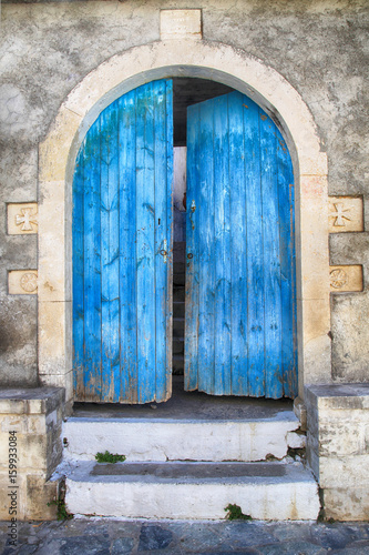 Old wall and blue wooden door, Greece