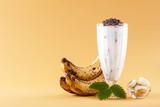 Milkshake with banana on yellow background