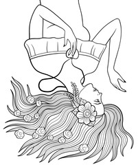 Young pretty girl with flower in her hair and heart-shaped pendant lying down on the ground with long hair spreading out. Antistress coloring page for adults.