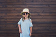 smiling girl in hat and sunglasses wooden background