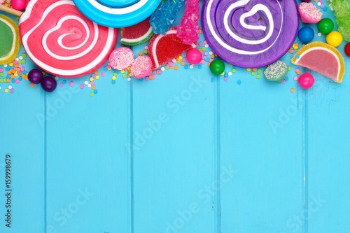 Top border of assorted colorful candies against a blue wood background