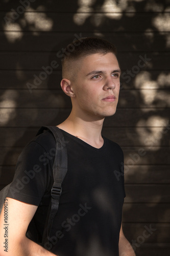 Teenage Boy looking at camera on background of Urban wall Poster