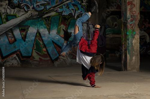 Female urban dancer standing on one hand