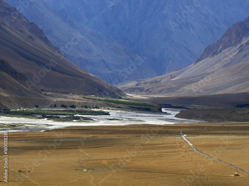 High mountain valley, in the foreground a huge yellow desert with a thread of the road, in the background a river among steep banks, the Himalayas.