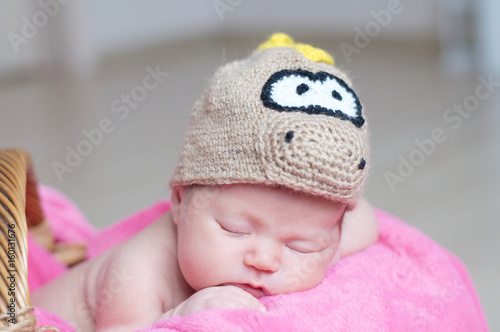 Cute happy newborn baby in dragon knitted cap sleeping in basket on pink blanket. Infant sleeping portrait.