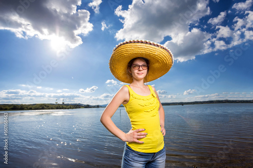young woman with sombrero on the beach with blue sky Poster