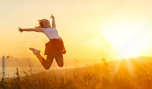 Leinwanddruck Bild Happy woman  jump,  rejoices,  on sunset in nature