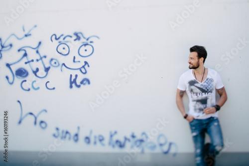 Mann lehnt an blau weißer Grafiti Wand