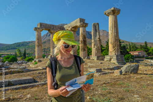 Greece tourist woman reads travel guide outdoors. Happy female holding informative guide at Doric Temple of Apollo in Ancient Corinth, Peloponnese. Acrocorinth on background. Tourism people concept.