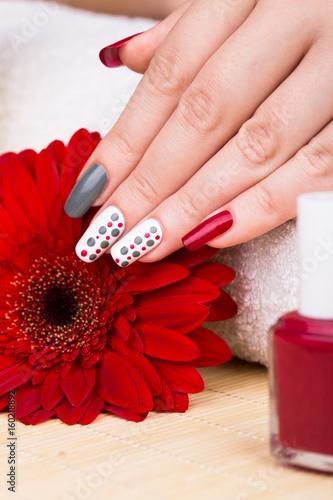 Manicure - Beauty treatment photo of nice manicured woman fingernails. Very nice feminine nail art with polka dots design. Selective focus. © tamara83
