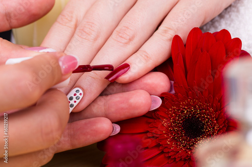 Manicure - Beauty treatment photo of nice manicured woman fingernails. Very nice feminine nail art with polka dots design. Selective focus. © tamara83