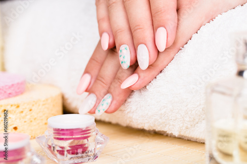 Manicure - Beauty treatment photo of nice manicured woman fingernails. Very nice feminine nail art with little flowers design and gentle colors. Selective focus. © tamara83