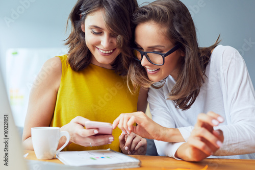 Female friends browsing internt on mobile phone Poster