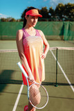 Woman with tennis racket poses on outdoor court