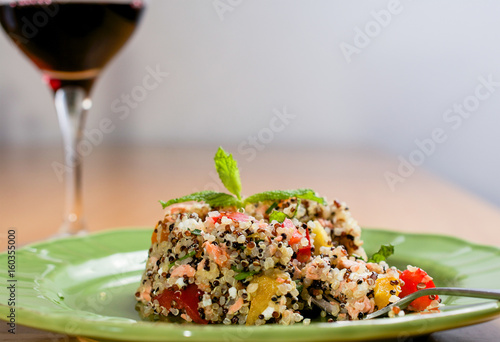 Closeup on green plate with tri-color quinoa salad on wooden table, with a glass Poster